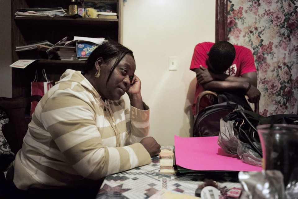 Marianne Jeune, left, a Haitian immigrant staying in the U.S. through the Temporary Protected Status program, sits in her Boston home while her son Amocachy Jeune, right, stands nearby. She has worked a variety of jobs caring for the elderly, and lost her home in Haiti in the 2010 earthquake.