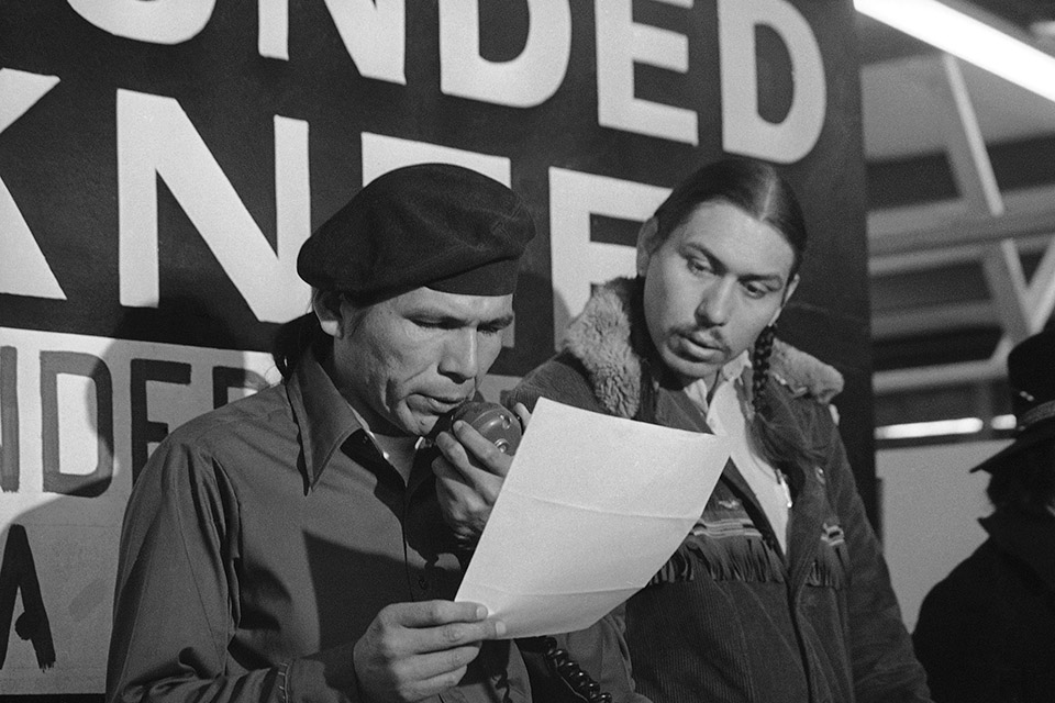 In this March 18, 1973, file photo taken in Wounded Knee, S.D., American Indian Movement leader Dennis Banks, left, reads an offer by U.S. government seeking to effect an end to the Native American takeover of Wounded Knee. Looking on is AIM leader Carter Camp. The family of Banks said he died Sunday, Oct. 29, 2017, at the age of 80. (AP Photo/Jim Mone, File)