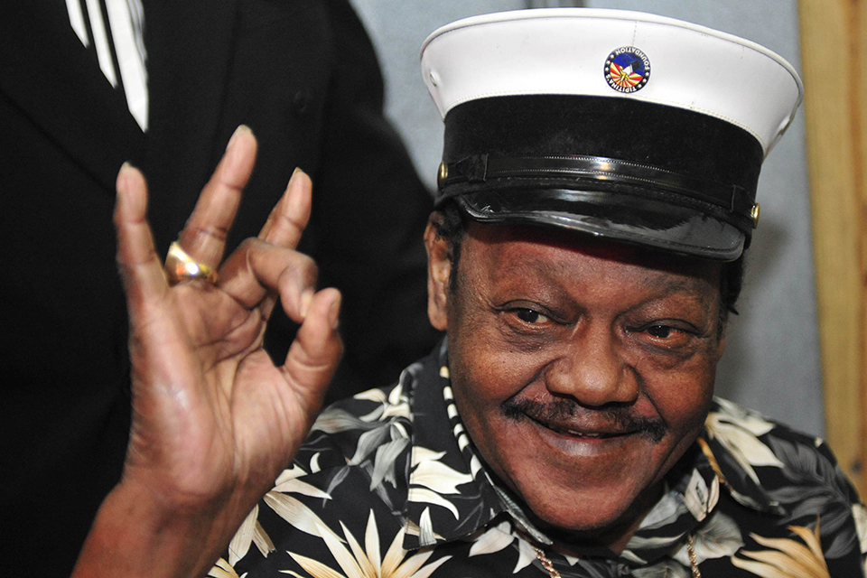 In this Nov. 5, 2008 file photo, Fats Domino waves to fans before a ceremony re-presenting two Grammy awards to replace the ones that he lost from Hurricane Katrina's flooding in New Orleans. Domino, the amiable rock 'n' roll pioneer whose steady, pounding piano and easy baritone helped change popular music even as it honored the grand, good-humored tradition of the Crescent City, has died. He was 89. Mark Bone, chief investigator with the Jefferson Parish, Louisiana, coroner's office, said Domino died Tuesday, Oct. 24, 2017. (AP Photo/Cheryl Gerber)