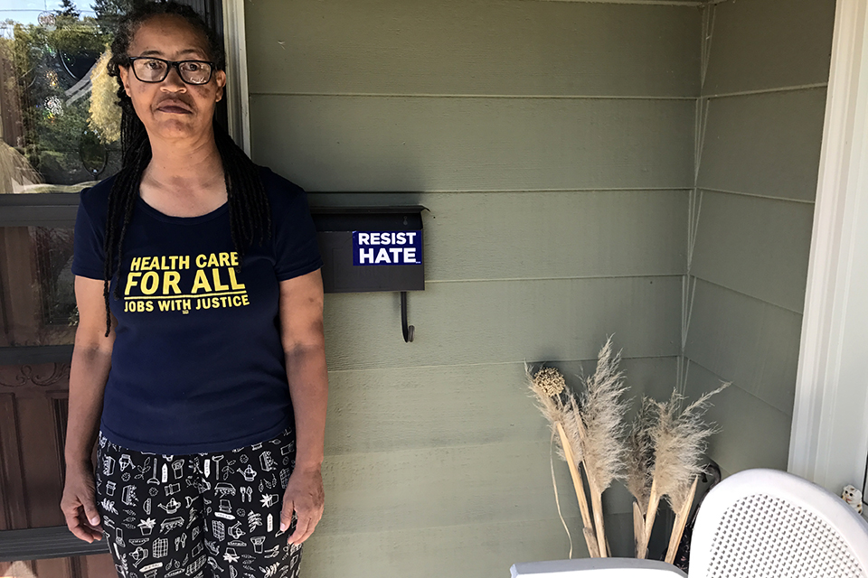 "Karen Wells standing next to mailbox with ""Resist Hate"" sticker"