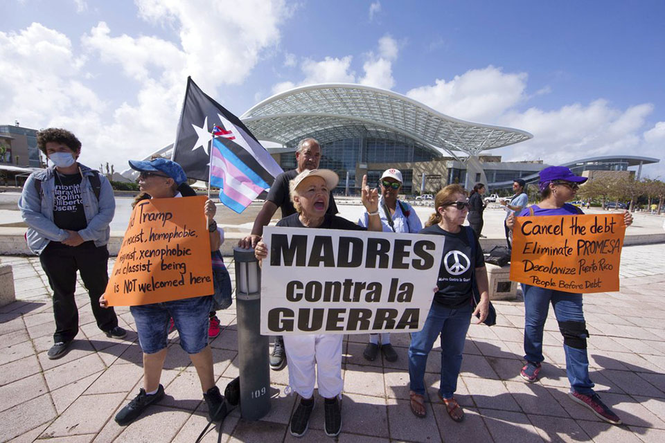 "Demonstrators gather outside the Convention Center to protest President Donald Trump's visit in San Juan, Puerto Rico, Tuesday, Oct. 3, 2017, in the wake of Hurricane Maria. The sign at center reads in Spanish ""Mothers against war."" Even before the storm hit on Sept. 20, Puerto Rico was in dire condition thanks to a decade-long economic recession that had left its infrastructure, including the island's power lines, in a sorry state. (AP Photo/Katja Torres)"