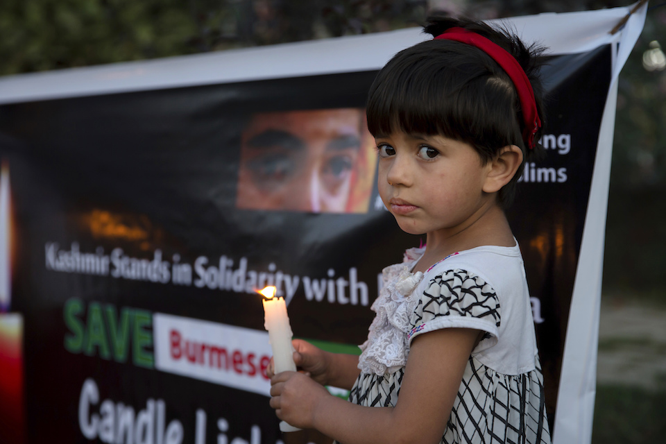 A Kashmiri girl holds a candle during a protest against the persecution of Myanmar's Rohingya Muslim minority, in Srinagar, Indian controlled Kashmir, Thursday, Sept. 7, 2017. Aid agencies were struggling to cope with a nonstop flood of Rohingya refugees into Bangladesh, where some 146,000 have arrived hungry and terrified after fleeing renewed violence in Myanmar. (AP Photo/Dar Yasin)