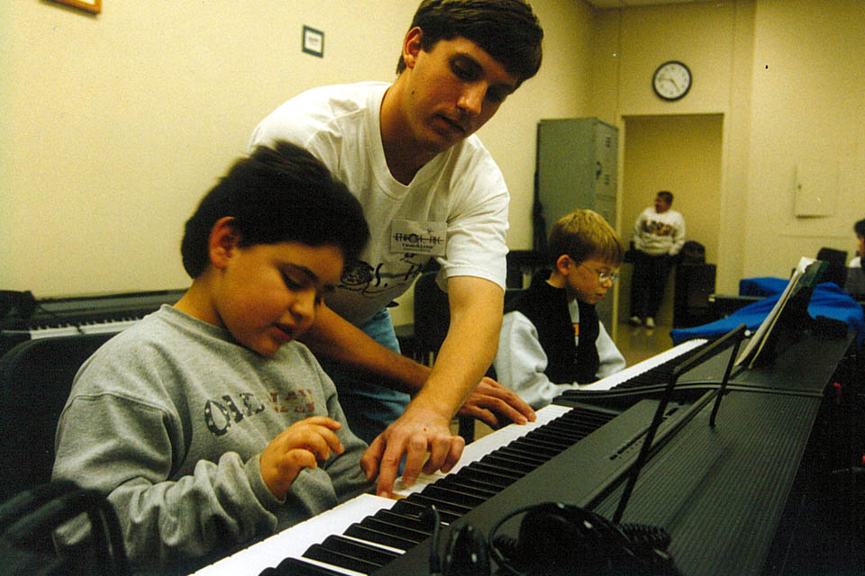 Man teaching child to play piano while another child practices nearby