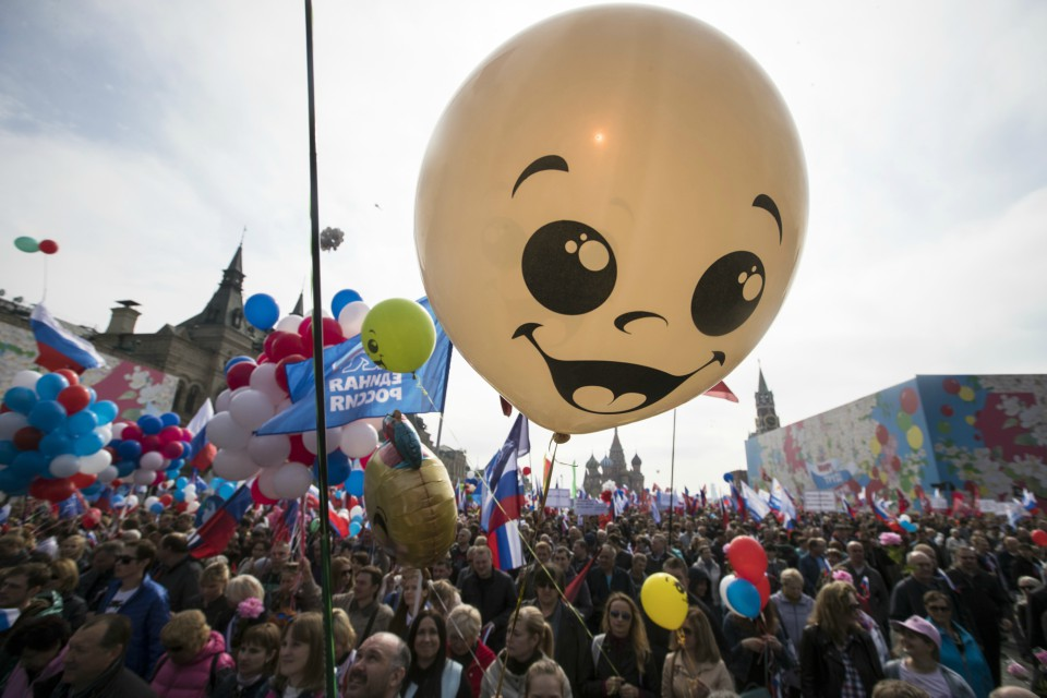 Balloons and flags fly over the crowd as people walk on Red Square to mark May Day in Moscow, with St. Basil's Cathedral center in the background (AP Photo/Pavel Golovkin)