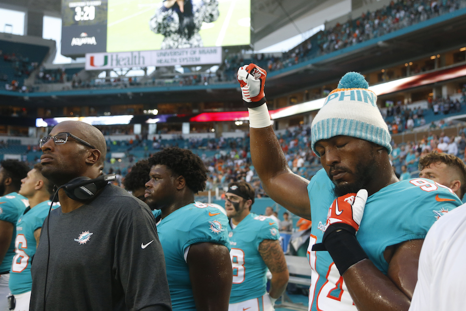 Miami Dolphins defensive end Robert Quinn (94) raises his right fist during the singing of the national anthem, before the team's NFL preseason football game against the Tampa Bay Buccaneers, Thursday, Aug. 9, 2018, in Miami Gardens, Fla. (AP Photo/Wilfredo Lee)