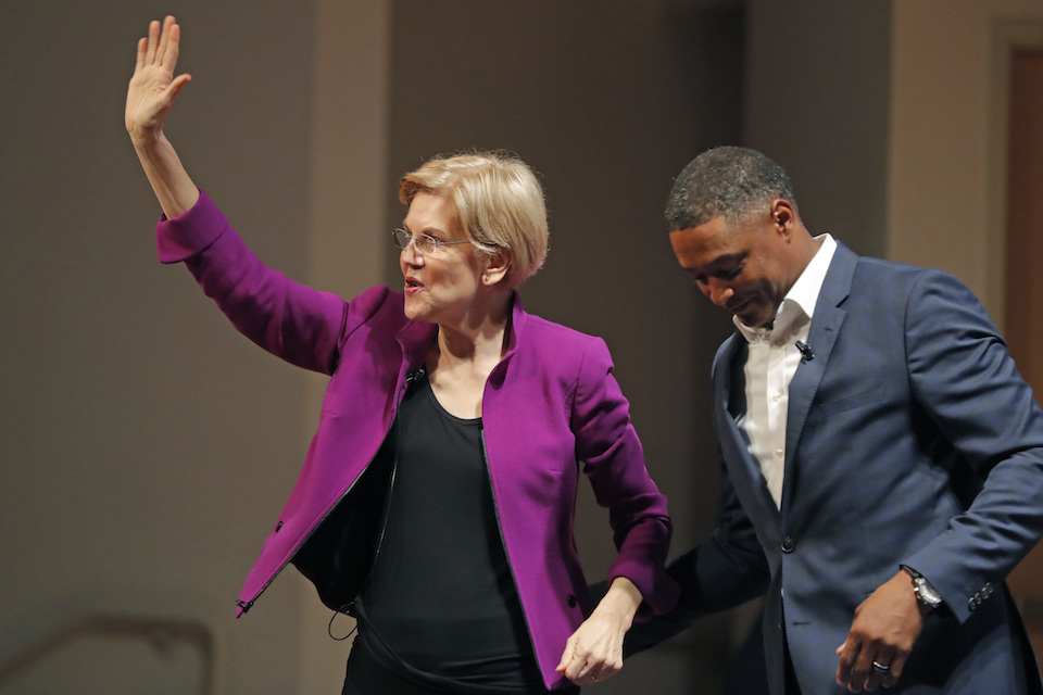 Sen. Elizabeth Warren, D-Mass., left, greets Rep. Cedric Richmond, D-La, and waves to the crowd as she arrives to speak in a sit-down conversation styled event at Dillard University in New Orleans, Friday, Aug. 3, 2018. (AP Photo/Gerald Herbert)
