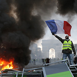 In this Nov. 24, 2018 file photo, a demonstrator waves the French flag on a burning barricade on the Champs-Elysees avenue with the Arc de Triomphe in background, during a demonstration against the rise of fuel taxes. There are parallels for unpopular French President Emmanuel Macron in the demise of King Louis XVI more than two centuries ago. Democracy has replaced monarchy but the culture of a mob taking its anger against perceived inequality onto the streets of Paris has not changed. (AP Photo/Michel Euler, File)