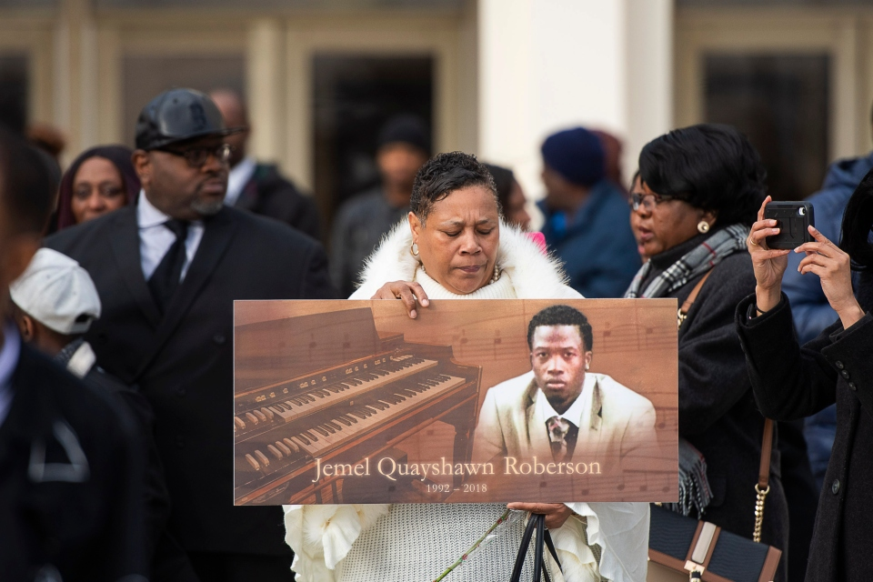 In this Nov. 8, 2018, file photo, a woman holds up a sign with Jemel Roberson's image at his funeral in Chicago. Roberson, who was working security at a bar, was killed on Nov. 11 while holding at gunpoint a man involved in a shooting in the barroom in Robbins, Ill. The recent shootings of Emantic Bradford Jr. and Roberson amplified long-held worries that bad things can happen when a black man is seen with a gun. (Tyler LaRiviere/Chicago Sun-Times via AP, File)
