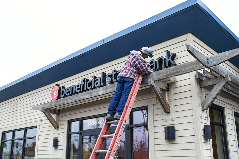 worker changing sign on Beneficial State Bank