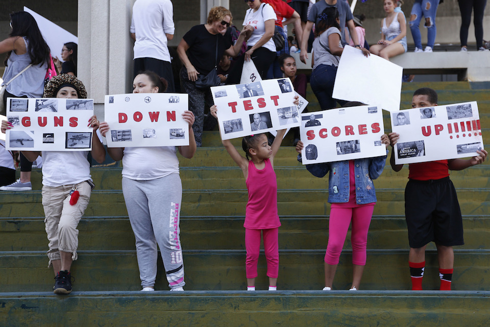 Children hold signs that read 'Guns Down Test Scores UP' during a protest against guns on the steps of the Broward County Federal courthouse in Fort Lauderdale, Fla., on Saturday, Feb. 17, 2018. Nikolas Cruz, a former student, is charged with killing 17 people at Marjory Stoneman Douglas High School in Parkland, Fla., on Wednesday. (AP Photo/Brynn Anderson)