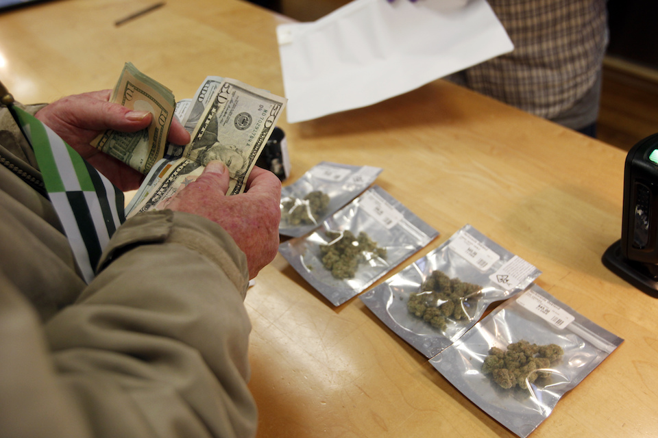 A customer purchases marijuana at Harborside marijuana dispensary in Oakland, Calif., Jan. 1, 2018. California's marijuana industry has been living off borrowed time _ most sales being made in the state's new legal market involve cannabis stockpiled by retailers last year. The transition to new weed is coming with an array of rules and testing and questions about whether it will get to store shelves. (AP Photo/Mathew Sumner, file)