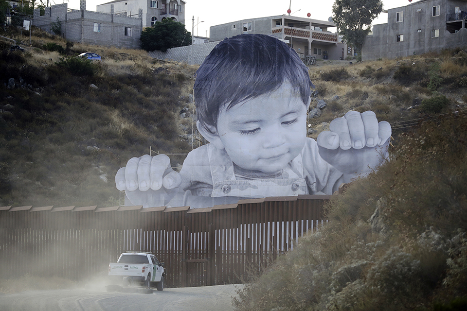 A Border Patrol vehicle drives in front of a mural in Tecate, Mexico, just beyond a border structure in Tecate, Calif.