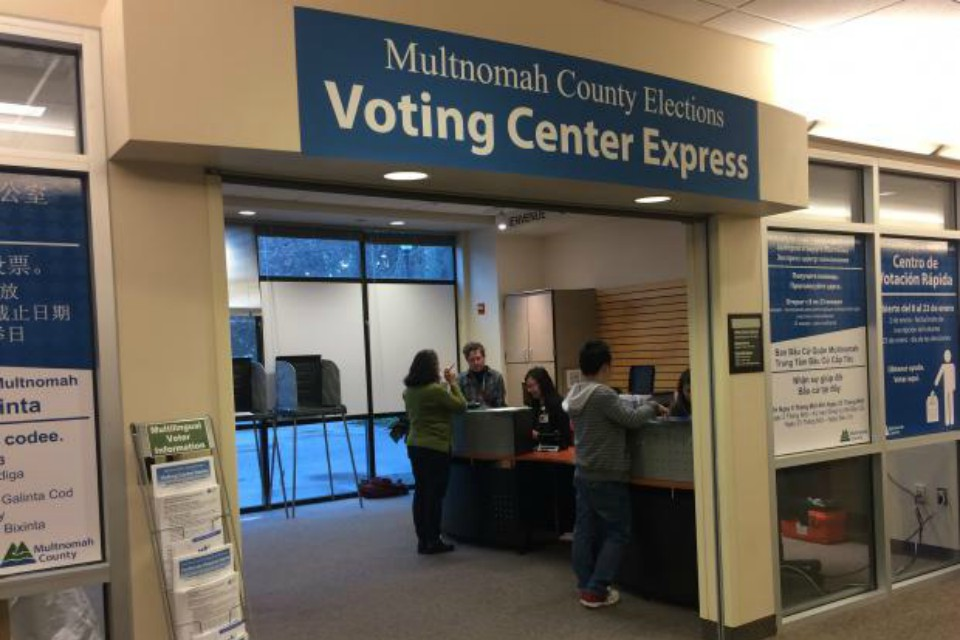 The Voting Center Express is open with voters getting assistance with replacement ballots at the front counter. Signs provide information in 6 languages.