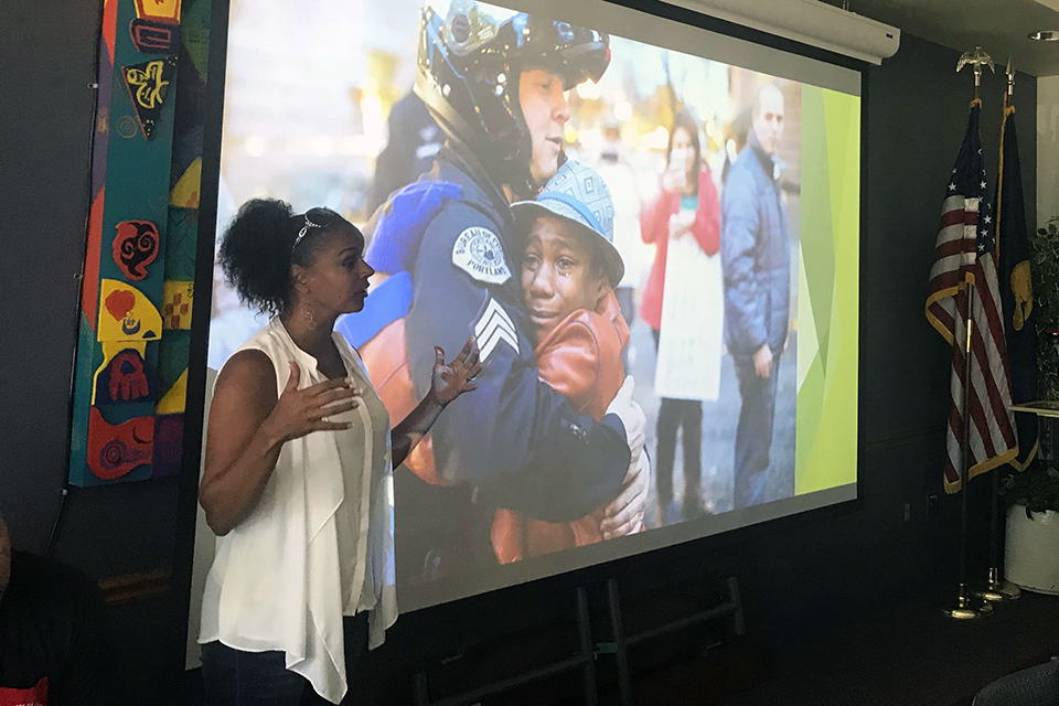 Nike Greene in front of slide photo of Devonte Hart with a Portland police officer