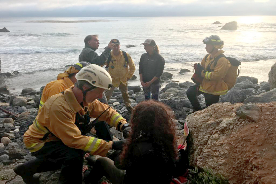 Authorities tend to Angela Hernandez, foreground center, after she was rescued, in Morro Bay, Calif. Authorities say a couple on a camping trip came upon Hernandez, from Oregon, who had been missing since July 6, after her car went over a cliff in coastal California. (Monterey County Sheriff's Office via AP)