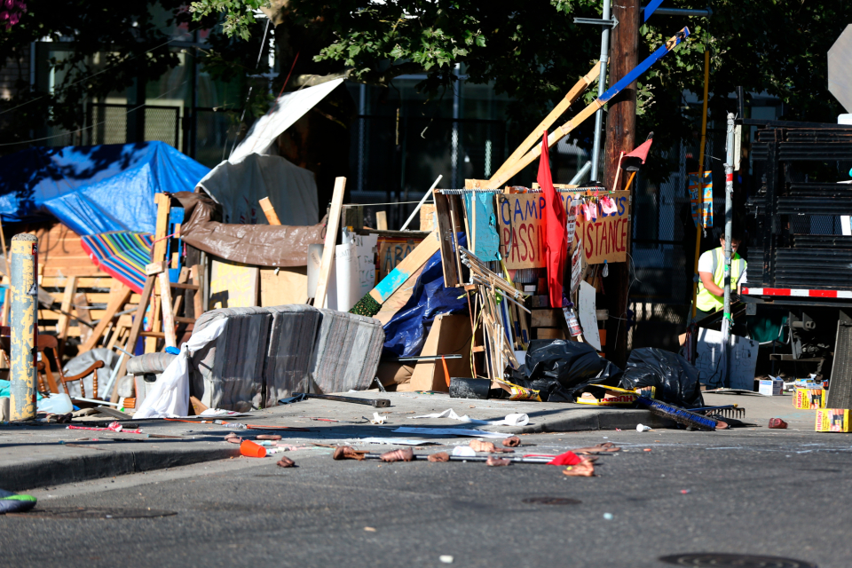 Portland police begin to clear the protest encampment at the Southwest Portland offices of the federal Immigration and Customs Enforcement agency on Wednesday, July 25, 2018. (Mark Graves/The Oregonian via AP)/The Oregonian via AP)