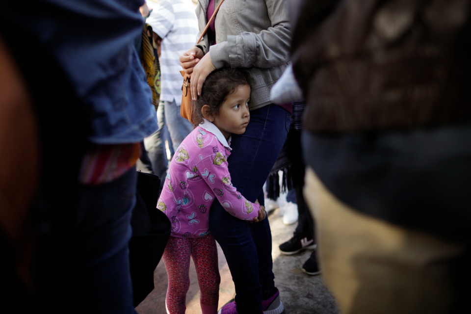Nicole Hernandez, of the Mexican state of Guerrero, holds on to her mother as they wait with other families to request political asylum in the United States, across the border in Tijuana, Mexico. The family has waited for about a week in this Mexican border city, hoping for a chance to escape widespread violence in their home state. (AP Photo/Gregory Bull)