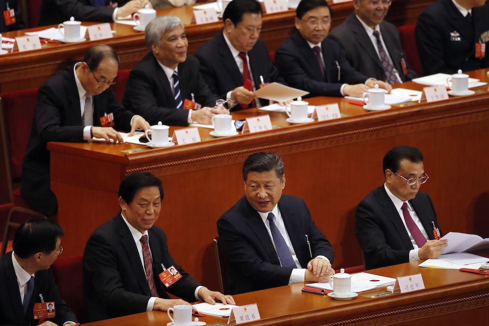 Chinese President Xi Jinping, center, talks to Li Zhanshu, a member of the Politburo Standing Committee, after casting their votes for an amendment to China's constitution that will abolish term limits on the presidency and enable Xi to rule indefinitely, during a plenary session of the National People's Congress at the Great Hall of the People in Beijing, Sunday, March 11, 2018. (AP Photo/Andy Wong)