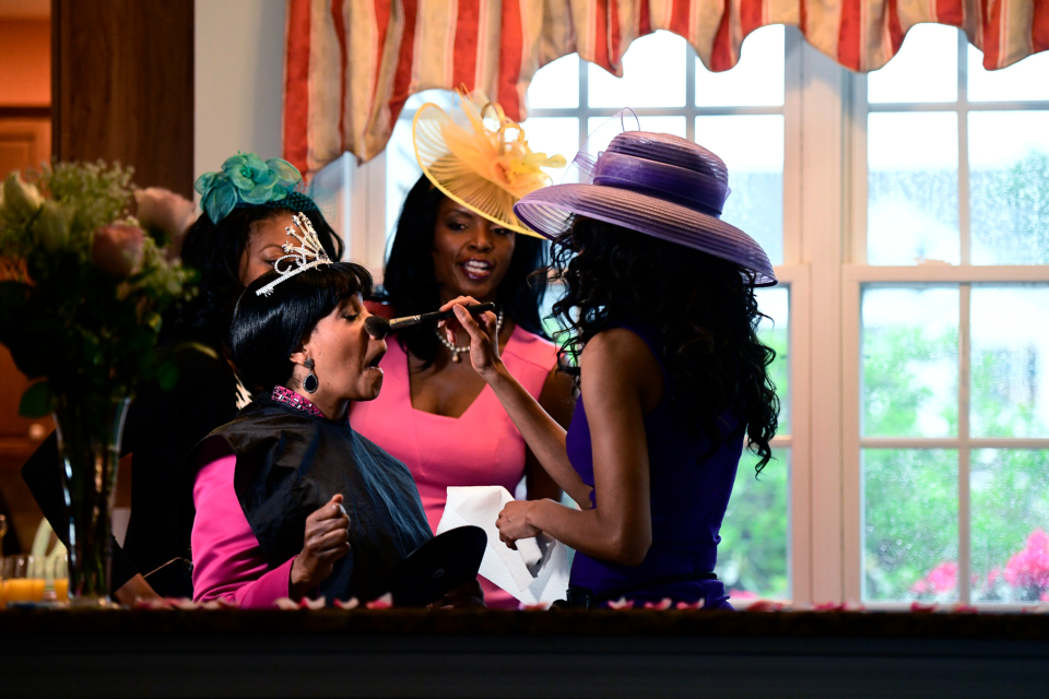 Paula Jackson of Philadelphia, left, receives makeup from makeup artist Pietra Dunmore, right, while Jenice Armstrong of Burlington, N.J. looks on during a television viewing party of the royal wedding of Meghan Markle and Prince Harry Saturday, May 18, 2018 (AP Photo/Corey Perrine)