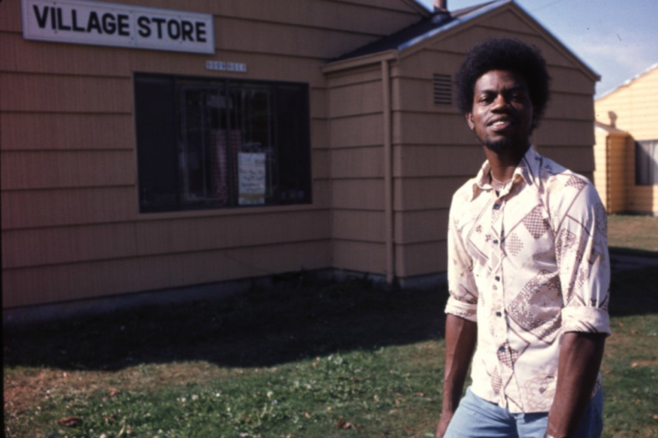 Young man in front of Columbia Villa Village Store portland