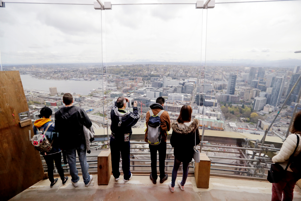 Visitors to the viewing platform of the Space Needle look east through newly-installed glass panels in Seattle. The family-owned landmark is set to unveil the biggest renovation in its 56 year history next month, a $100 million investment in a single year of construction that transformed the structure's top viewing level some 500-feet above ground. (AP Photo/Elaine Thompson)