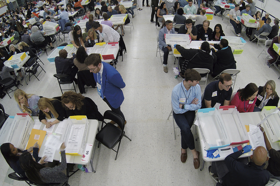Workers at the Broward County Supervisor of Elections office, foreground, show Republican Democrat observers ballots during a hand recount, Friday, Nov. 16, 2018, in Lauderhill, Fla. (AP Photo/Wilfredo Lee)