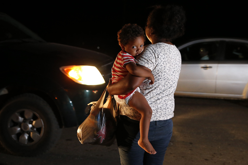 Honduran migrant Luz Padilla Valverde, carrying her child, begs for contributions of one peso (5 cents) from passing drivers, as a thousands-strong caravan of Central Americans hoping to reach the U.S. border stops for the night, in Matias Romero, Oaxaca state, Mexico, Thursday, Nov. 1, 2018. Most of the main caravan of Central American migrants spent a rain-drenched night outside, before continuing their slow walk through southern Mexico.(AP Photo/Rebecca Blackwell)