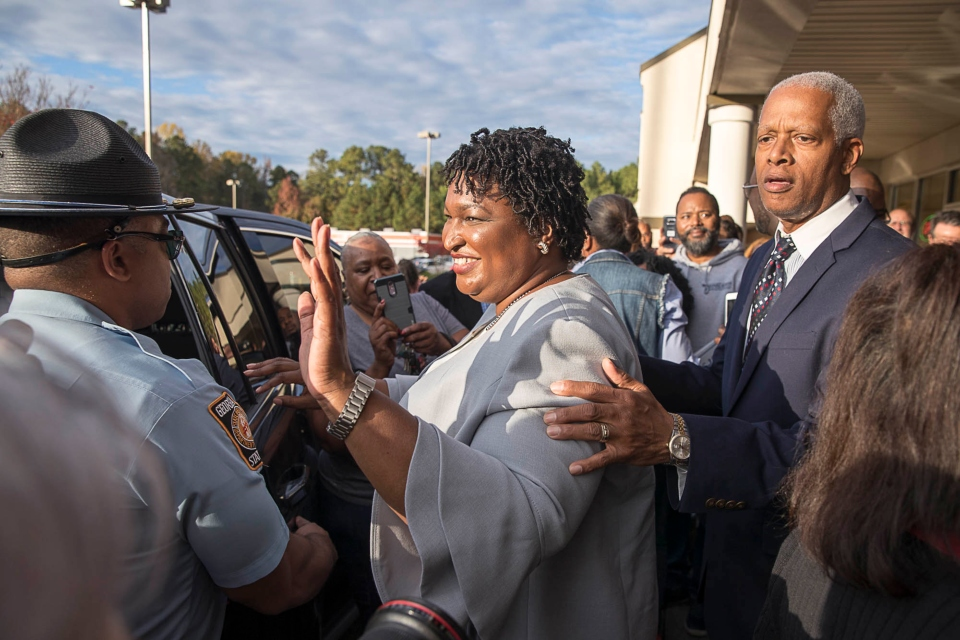 U.S. Rep. Hank Johnson, right, escorts Georgia gubernatorial candidate Stacey Abrams through a crowd of supporters during a campaign stop at the Deshon Plaza Shopping Center in Stone Mountain, Tuesday, Nov. 6, 2018. (Alyssa Pointer /Atlanta Journal-Constitution via AP)