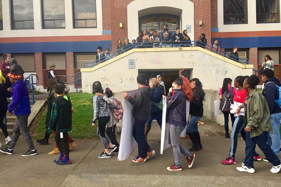 Students walk past Jefferson High School Feb. 9 at a walkout that began at Ockley Green Middle School. On Tuesday Portland Public Schools announced it would not fire Chris Riser, an Ockley Green teacher placed on leave in connection with that protest. Photo by Kate Nacy.