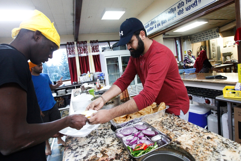 In this Oct. 3, 2018 photo, Karandeep Singh, right, and Abdoulaye Camara, both who were recently released from the nearby federal prison in Sheridan, Ore., serve up food at the Dasmesh Darbar Sikh temple in Salem, Ore. After Trump's zero-tolerance policy recently sent immigrant detainees to a federal prison in rural Oregon, more than 100 lawyers, retirees, recent college graduates, clergy and others in the area stepped up to help out. (AP Photo/Amanda Loman)