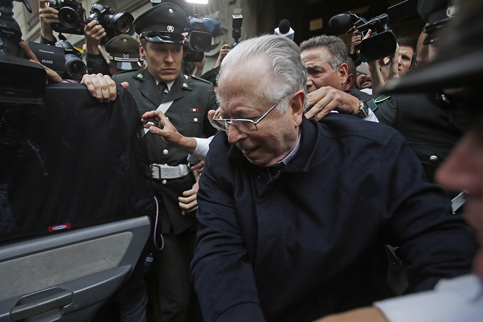 "In this Nov. 11, 2015 file photo, Fernando Karadima is escorted from a court, after testifying in a case that three of his victims brought against the country's Catholic Church in Santiago, Chile. Pope Francis has on Friday, Sept. 29, 2018, defrocked Karadima, a priest at the center of the global sex abuse scandal rocking his papacy, invoking his ""supreme"" authority to stiffen a sentence originally handed down by a Vatican court in 2011. (AP Photo/Luis Hidalgo, File)"
