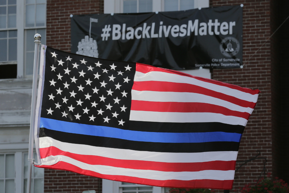 "In this July 28, 2016, file photo, a flag with a blue and black stripes in support of law enforcement officers, flies at a protest by police and their supporters outside Somerville City Hall in Somerville, Mass. An Oregon county has agreed to pay $100,000 to a black employee who sued after a co-worker pinned up a ""Blue Lives Matter"" flag. The Oregonian/OregonLive reports Saturday, April 20, 2019, that Karimah Guion-Pledgure alleged in her January lawsuit that the flag demeans the ""Black Live Matter"" movement. (AP Photo/Charles Krupa, File)"