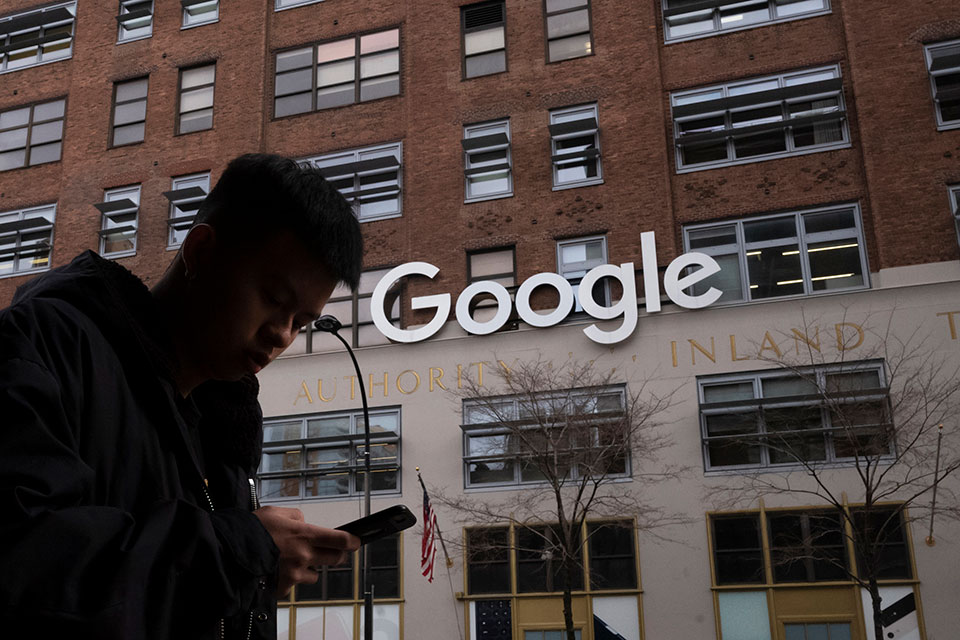 A man using a mobile phone walks past Google offices