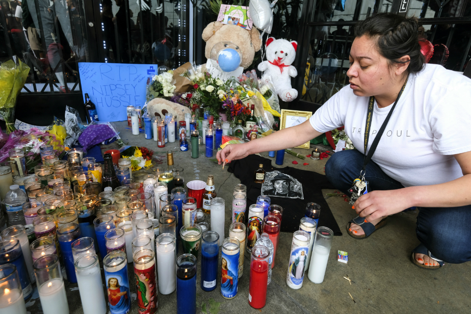 Jennifer Chavez lights candles at a makeshift memorial in front of the Marathon Clothing store of rapper Nipsey Hussle in Los Angeles. (AP Photo/Ringo H.W. Chiu)