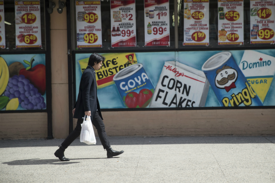 A man leaves a supermarket in the East Village neighborhood of Manhattan carrying his groceries in a plastic bag, Wednesday, March 27, 2019. Two New York lawmakers say Wednesday that they're optimistic that a ban on single-use plastic shopping bags could be included in the spending plan that's due Sunday. (AP Photo/Mary Altaffer)