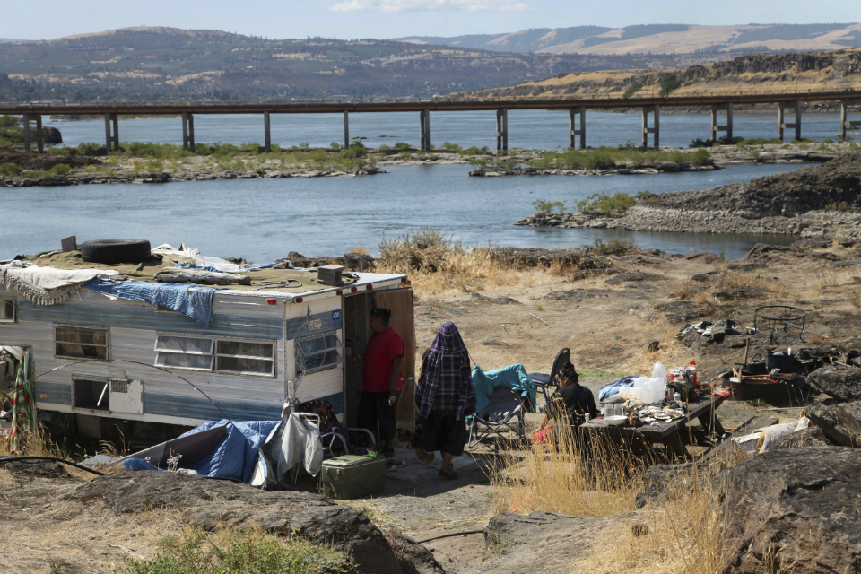 This Aug. 22, 2014, file photo shows the home of Ranetta Spino and her family at the river's edge at Lone Pine, a Native American fishing site on the Columbia River near The Dalles, Ore. Federal legislation to assess 31 tribal fishing sites in Oregon and Washington and make critical improvements to sewer and water systems has passed the U.S. House after three years of delays. (AP Photo/Gosia Wozniacka, File)