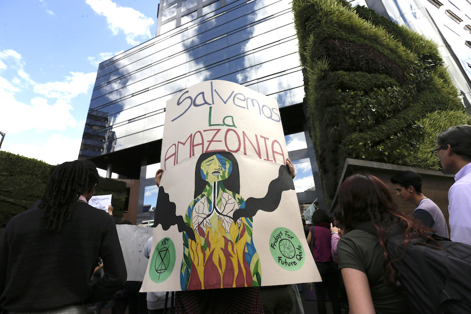 People gather outside the Brazilian embassy during a demonstration demanding something be done about the fires that have been breaking out at an unusual pace in Brazil this year, causing global alarm over deforestation in the Amazon region, in Quito, Ecuador, Friday, Aug. 23, 2019. Under increasing international pressure to contain fires sweeping parts of the Amazon, Brazilian President Jair Bolsonaro on Friday authorized use of the military to battle the massive blazes. (AP Photo/Dolores Ochoa)