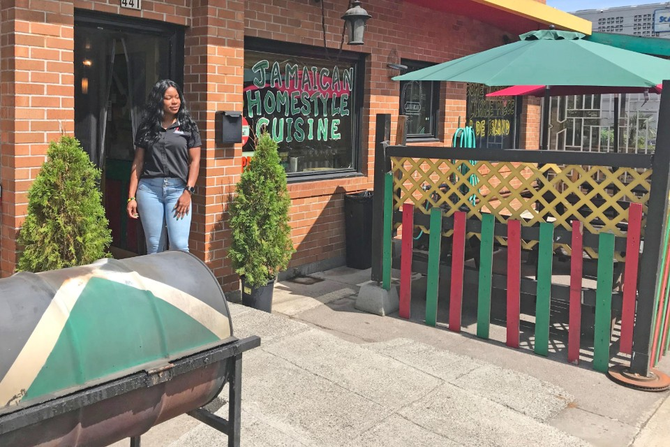 In this photo, Keacean Phillips, owner of Jamaican Homestyle Cuisine, poses outside of her restaurant located on North Killingsworth. (Photo by R. Dallon Adams)
