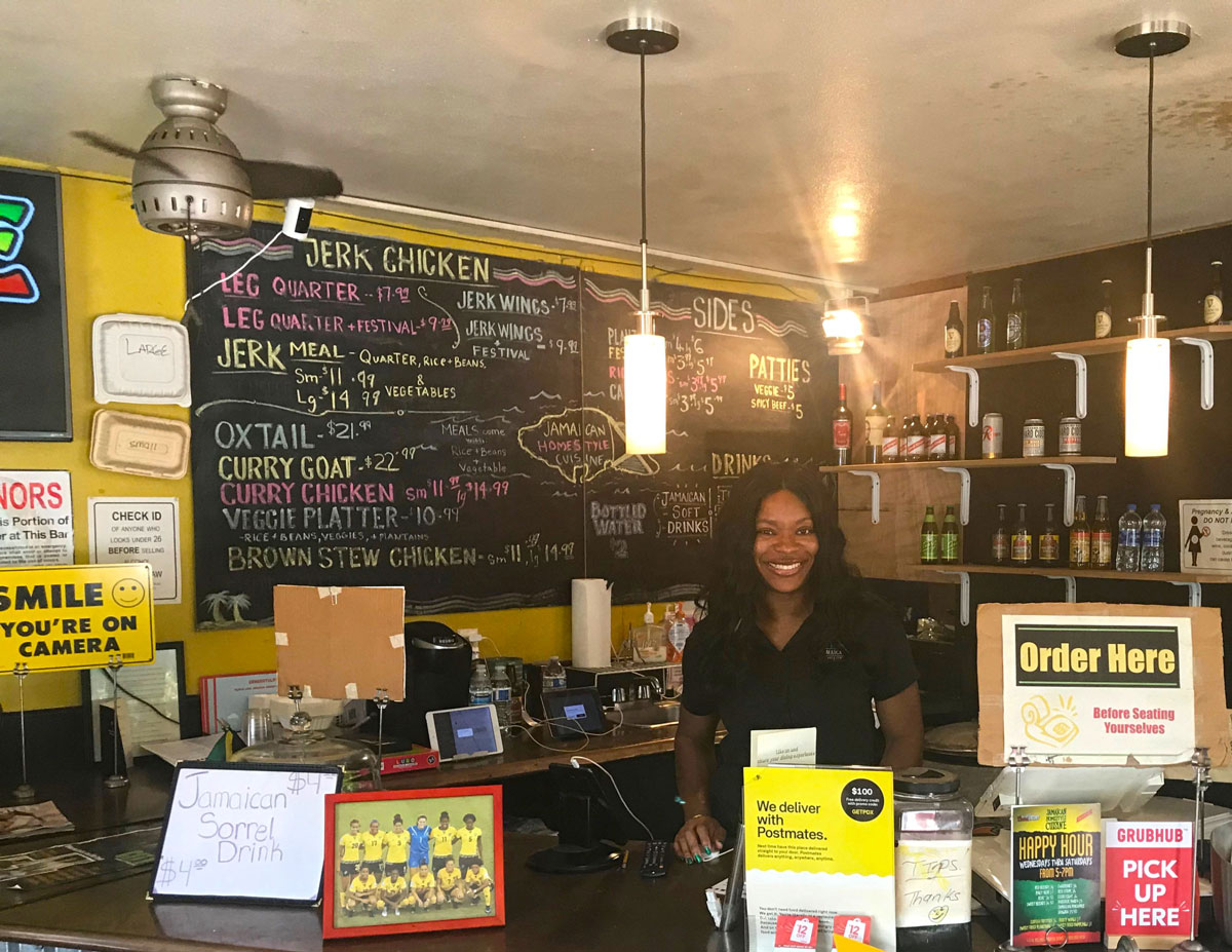 Keacean Phillips, owner of Jamaican Homestyle Cuisine, poses behind the register at her restaurant. (Photo by R. Dallon Adams