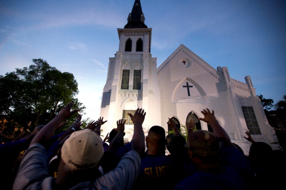 FILE - In this June 19, 2015, file photo, the men of Omega Psi Phi Fraternity Inc. lead a crowd of people in prayer outside the Emanuel AME Church after a memorial in Charleston, S.C. As the Democratic presidential field grapples with how to address a pair of shootings that killed 31, candidate Sen. Cory Booker, D-N.J., is making a gun policy speech Aug. 7, 2019, in the historic South Carolina church that's become synonymous with hate-fueled attacks on people of faith. (AP Photo/Stephen B. Morton, File)