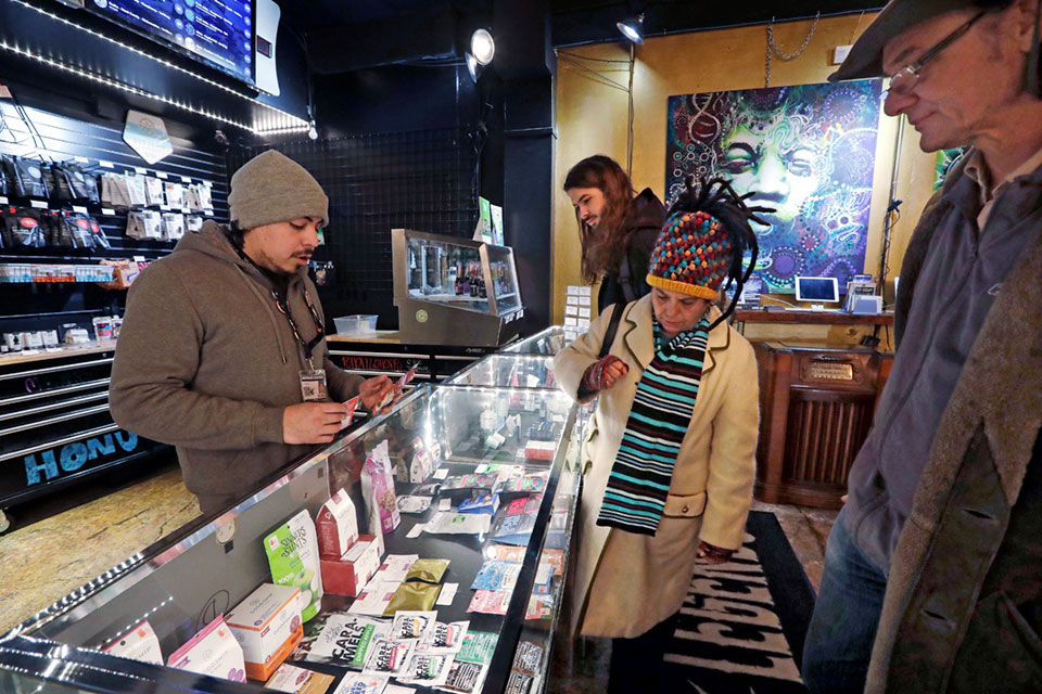 cannabis consultant Juan Aguilar, left, assists customers Bill, right, and Nize Nylen and their son Russell shop for edible marijuana products in the Herban Legends pot shop in Seattle