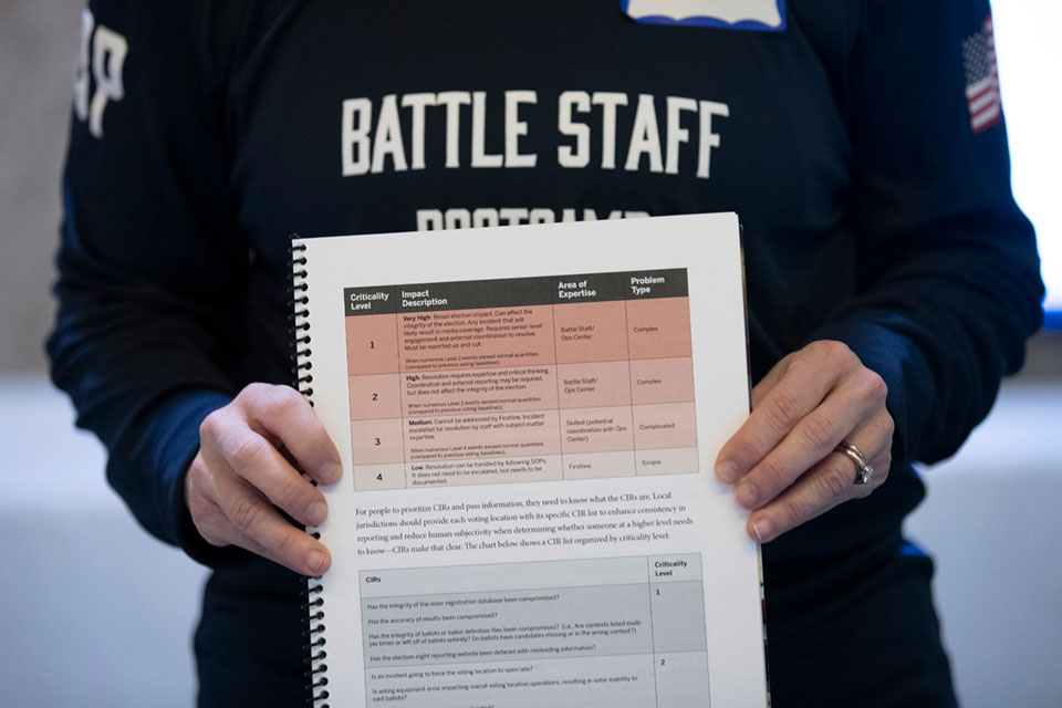 In this Monday, Dec. 16, 2019, photo, a booklet is held up during an exercise run by military and national security officials, for state and local election officials to simulate different scenarios for the 2020 elections, in Springfield, Va