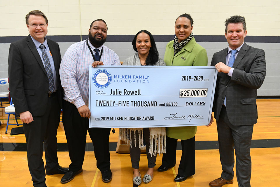 Julie Rowell (center) gets a hand with her oversized Milken Educator Award check. From left, Oregon Superintendent of Public Instruction Colt Gill; Gresham High School Principal Drake Shelton; recipient Julie Rowell; Gresham-Barlow School District Superintendent Dr. A. Katrise Perera; and Greg Gallagher, senior program director for the Milken Family Foundation