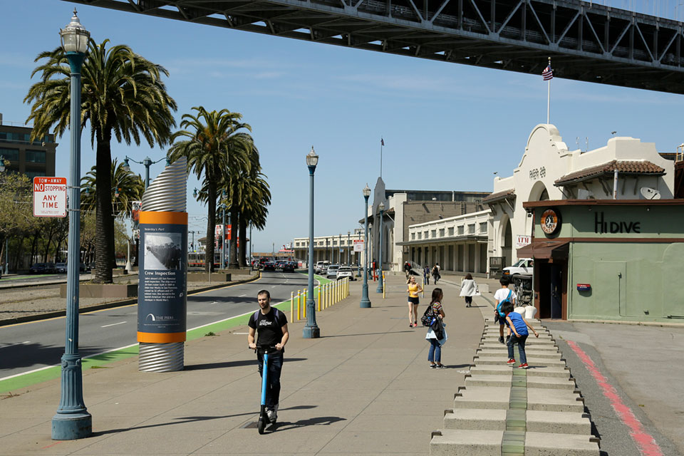 a man rides a scooter near children playing along the Embarcadero in San Francisco