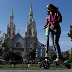 a woman rides a motorized scooter in Washington Square Park in San Francisco
