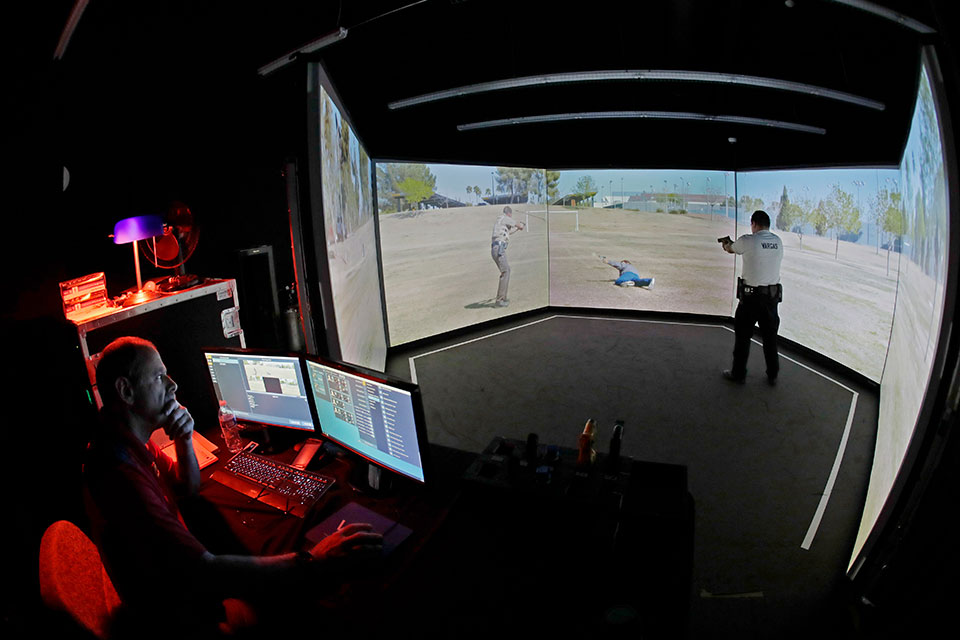 In this July 16, 2019, photo, an officer, right, at Washington state's Basic Law Enforcement Academy, takes part in an exercise using an immersive virtual firearms training simulator in Burien, Wash