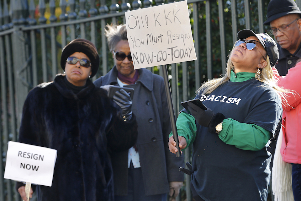 Tara Raigns, of Petersburg, Va., right, reacts to Gov. Ralph Northam's comments during a news conference in the Governor's Mansion in Richmond, Va., on Saturday, Feb. 2, 2019. She joined protesters outside, calling for his resignation. (Alexa Welch Edlund/Richmond Times-Dispatch via AP)