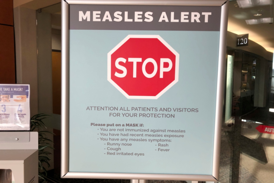 In this Jan. 30, 2019 file photo signs posted at The Vancouver Clinic in Vancouver, Wash., warn patients and visitors of a measles outbreak. A measles outbreak near Portland, Ore., has revived a bitter debate over so-called personal belief exemptions to childhood vaccinations. Four percent of Washington secondary school students have non-medical vaccine exemptions. (AP Photo/Gillian Flaccus,File)