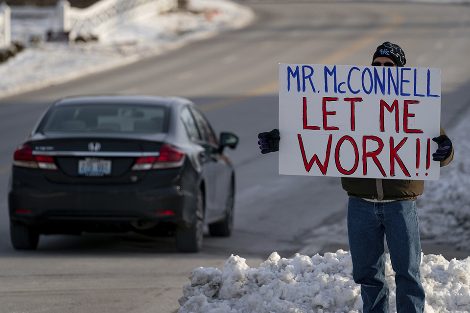 Furloughed EPA worker Jeff Herrema holds a sign outside the offices of U.S. Senator Mitch McConnell, in Park Hills, Ky., Tuesday, Jan 22, 2019. (AP Photo/Bryan Woolston)