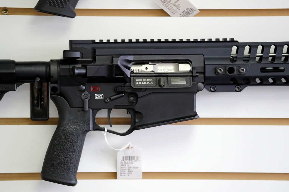 "In this Oct. 2, 2018, file photo, a semi-automatic rifle, with ""God Bless America"" imprinted on it, is displayed for sale on the wall of a gun shop in Lynnwood, Wash. Starting Tuesday, Jan. 1, 2019, no one under the age of 21 in Washington state will be allowed to purchase a ""semi-automatic assault rifle,"" under a voter-approved initiative that passed in November. (AP Photo/Elaine Thompson, File)"
